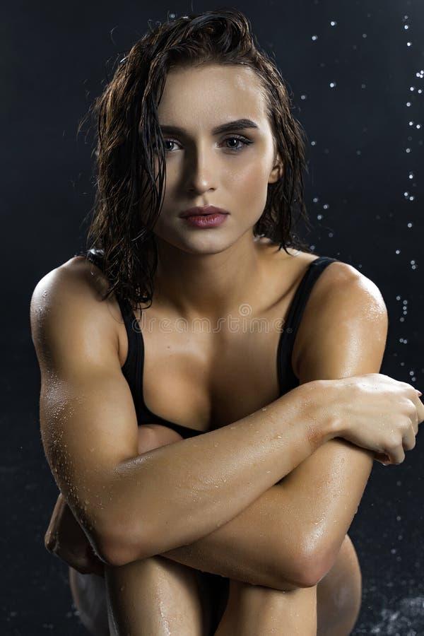 美好的腿长和赃物运动健身女孩模型,穿一件黑体育内衣,有湿油性皮肤的,休息坐下 库存图片