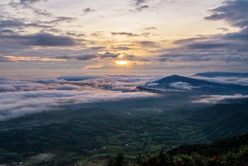 美好的自然风景太阳在盖山和明亮的天空在日出期间在冬天的海雾上 库存图片