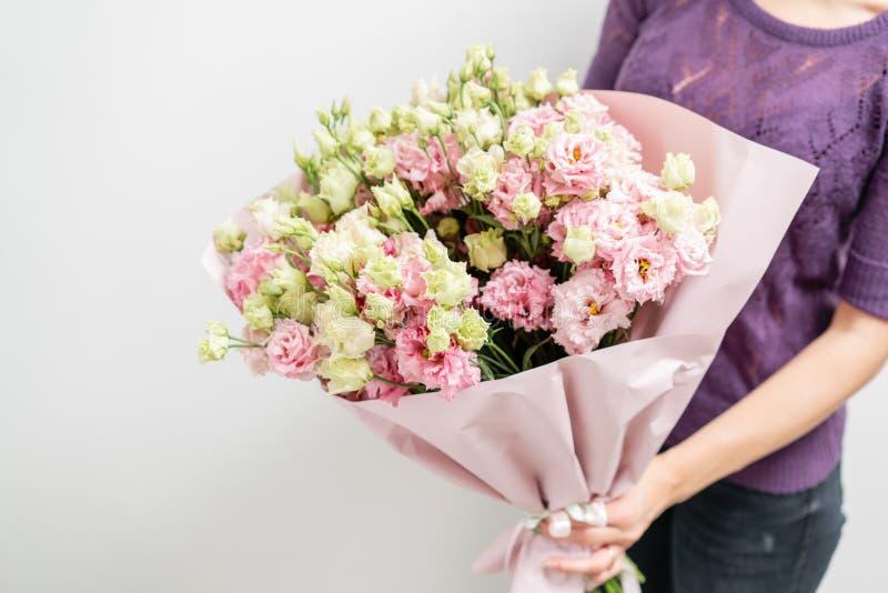 美好的花束春天 举行与桃红色颜色lisianthus的女孩花的布置  围住白色 图库摄影