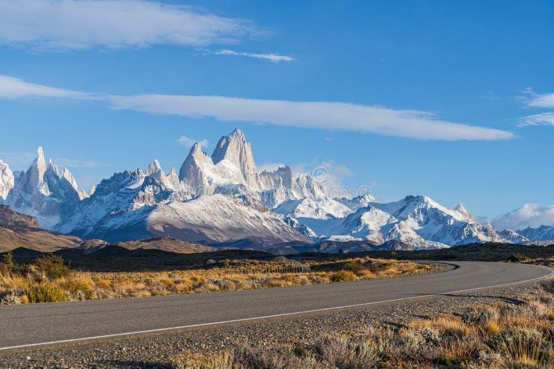 美好的菲茨罗伊峰和托雷峰峰顶在早晨天空蔚蓝的雪山与在柏油路旁边的金黄黄色草 免版税库存图片