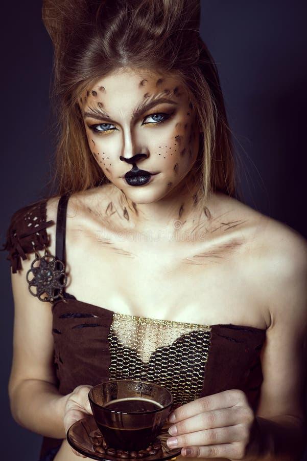 年轻美好的蓝眼睛的模型画象与拿着一杯咖啡的艺术性的豹子构成的用在茶碟的豆 免版税库存图片