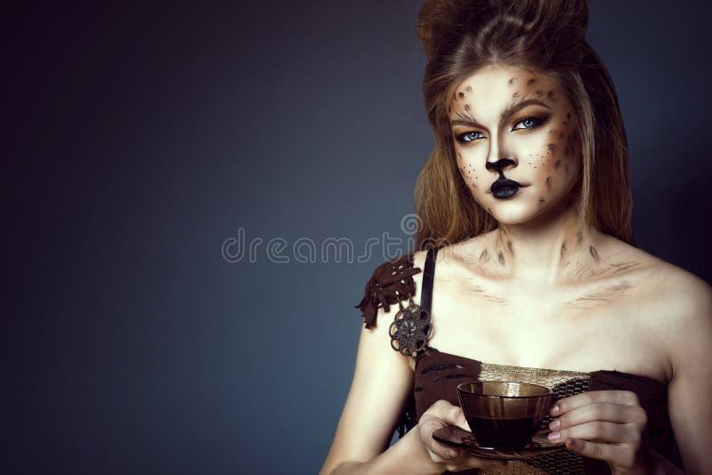 年轻美好的蓝眼睛的模型画象与艺术性的豹子拿着一杯咖啡的构成和掠过的头发的 免版税库存图片