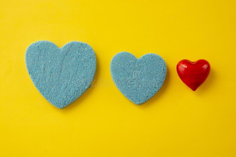 美好的蓝色和红心 招呼ard为华伦泰s天 运动沙子心形,在黄色背景 创造性的重点 免版税库存照片