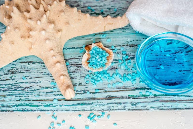 美好的蓝色温泉构成 蓝色海盐、液体皂、海星、壳和一条白色毛巾 库存照片