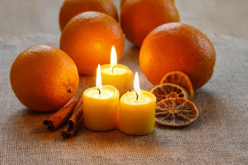 美好的蜡烛和水多的桔子在黄麻桌布 库存照片