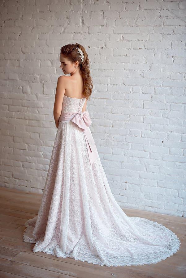 美好的豪华女性模型全长画象与中等棕色头发的在一件长的白色礼服在屋子里 免版税库存图片