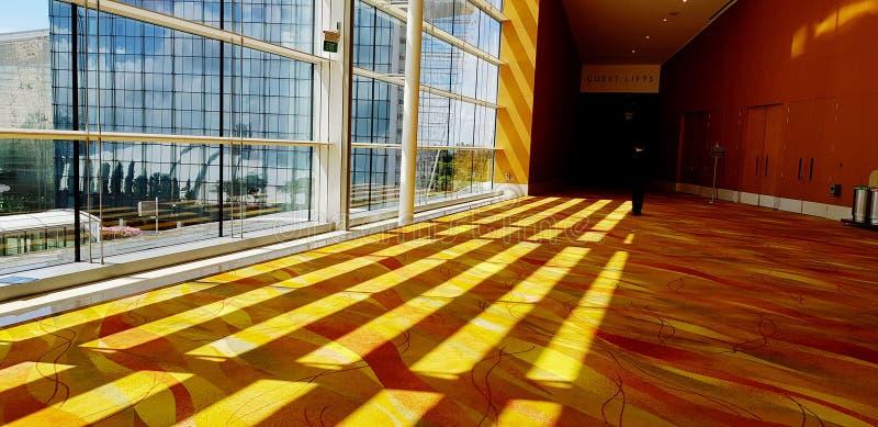 美好的轻的样式和阴影线在从大厦的外面发光的黄色地毯 库存图片