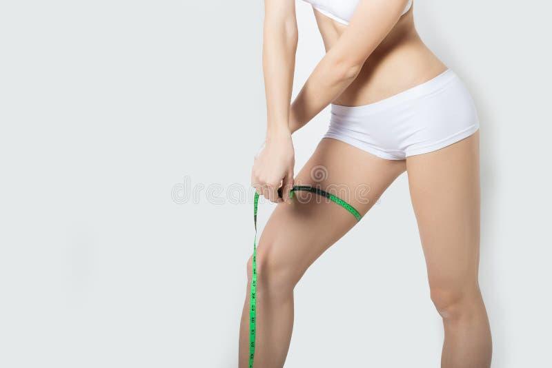 年轻美好的运动女孩测量磁带,健康生活方式,健身,锻炼,健康微小的身体的措施大腿和腿 图库摄影