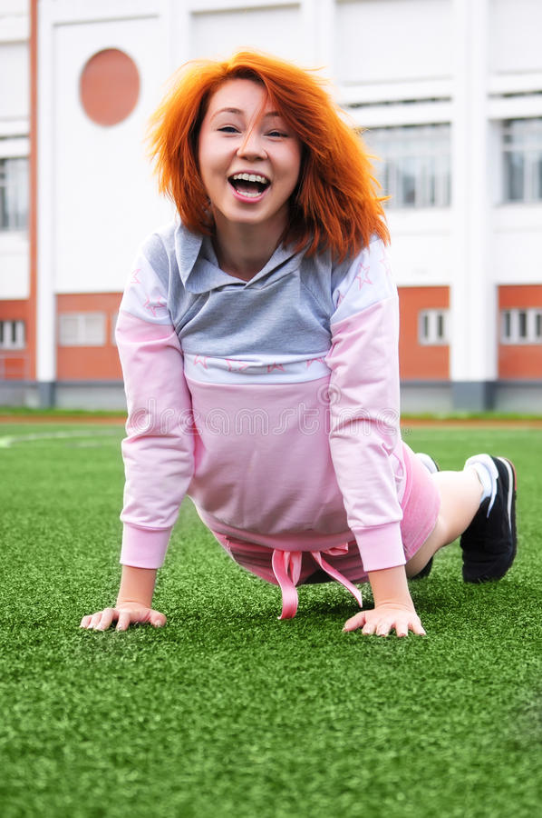 美好的运动的红发女孩笑和笑话在体育期间 库存照片