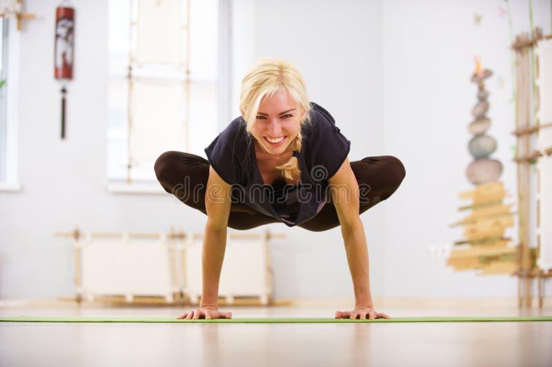 美好的运动的适合信奉瑜伽者妇女实践瑜伽asana帕德马Bakasana莲花起重机姿势在健身屋子 库存照片