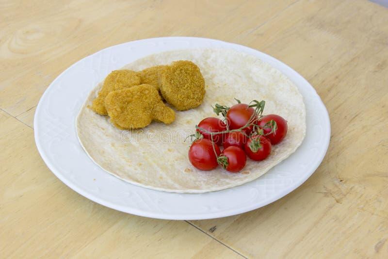 美好的透视射击了鸡块和小红色新鲜的蕃茄在宽白色板材作为一顿早餐用稀薄的面包 图库摄影