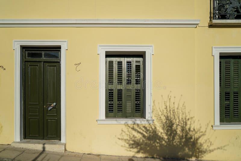 美好的都市大厦门面背景场面在淡色奶油色黄色膏药油漆墙壁,橄榄绿木入口的 库存照片