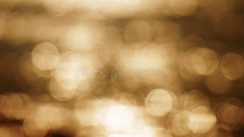 美好的金摘要闪烁的光bokeh背景 在日落的闪耀的和闪烁海洋表面 库存图片