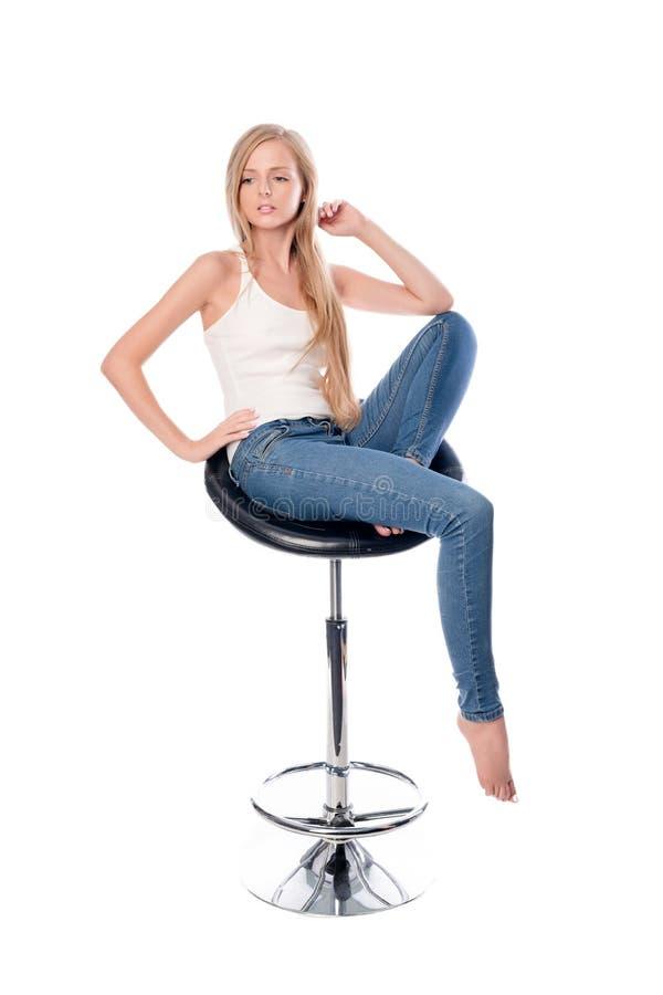 年轻美好的长发妇女就座的垂直的射击在白色背景隔绝的办公室或酒吧椅子的 免版税库存图片