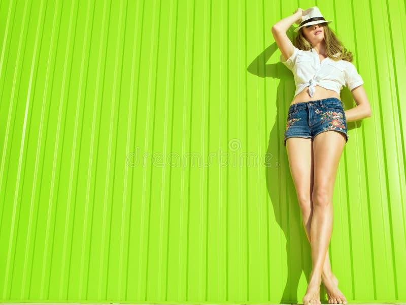 年轻美好的长腿的模型画象在白色的阻塞了衬衣、牛仔裤短裤与花装饰品和巴拿马 免版税库存照片