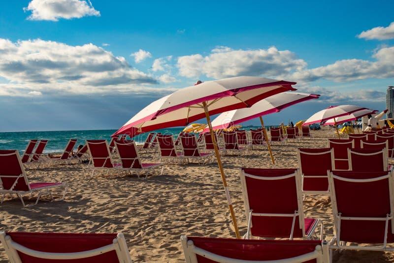 美好的颜色对比:天空蔚蓝和红色sunbeds在南海滩,迈阿密 库存图片