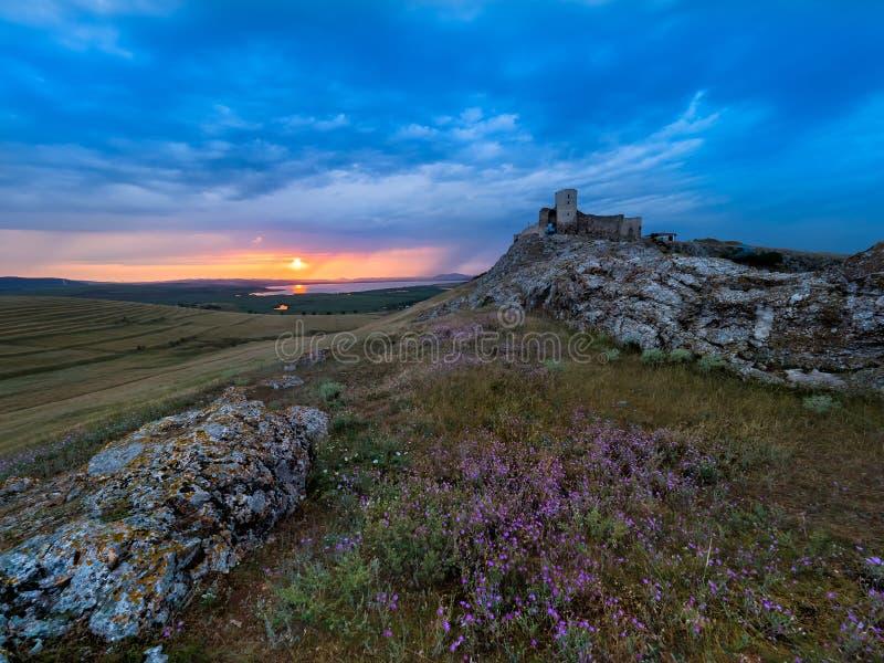 美好的风景和剧烈的日落天空与暴风云在Enisala老堡垒城堡 免版税库存图片