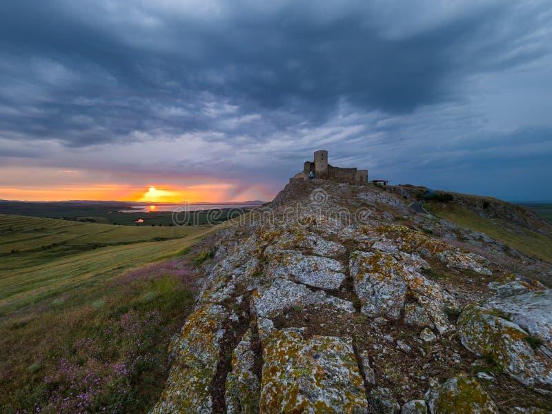 美好的风景和剧烈的日落天空与暴风云在Enisala老堡垒城堡 免版税库存照片
