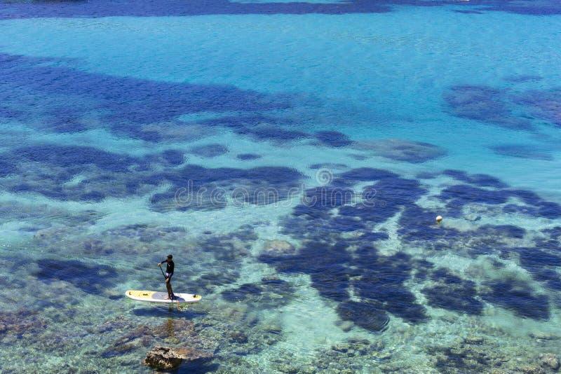 美好的风景在蓝色海洋伊维萨岛在与人实践的桨海浪的一好日子 夏天和假日概念 库存照片