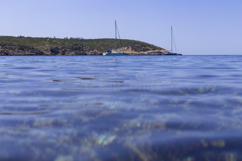 美好的风景在蓝色海洋伊维萨岛在与小船的一好日子在天际 夏天和假日概念 免版税库存照片