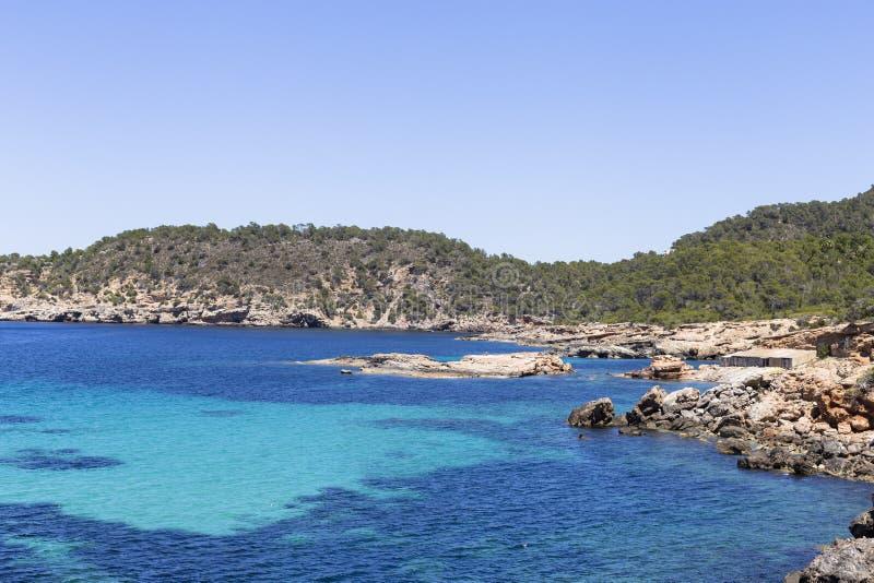 美好的风景在蓝色海洋伊维萨岛在与小船的一好日子在天际 夏天和假日概念 库存图片
