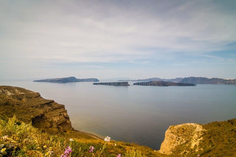 美好的风景有卡美尼岛,一个小希腊海岛的海视图在圣托里尼附近的爱琴海 免版税图库摄影