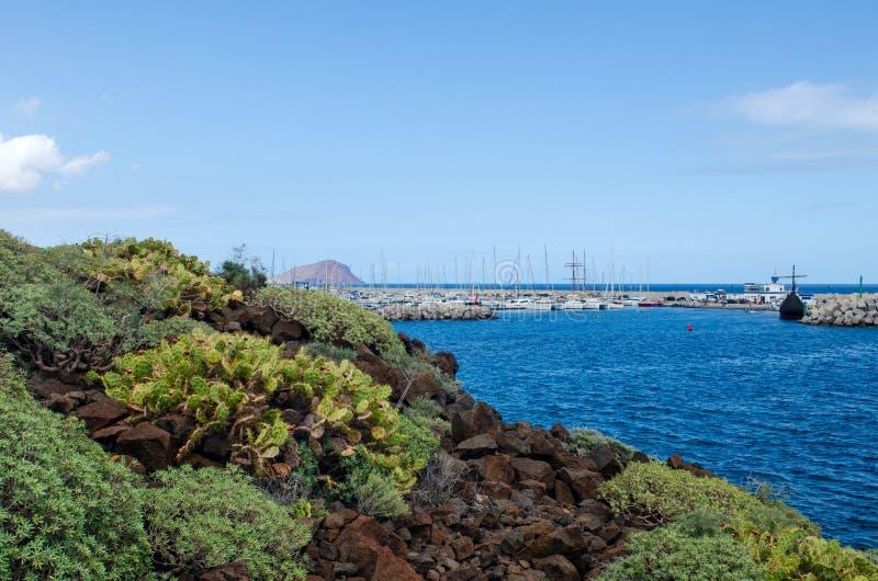 美好的风景有岩石海岸线、大西洋和小游艇船坞圣米格尔火山的看法 南的特内里费岛,加那利群岛,西班牙 免版税库存图片