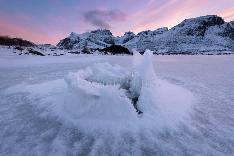 美好的风景裂化的冰,冻沿海有山在日落在罗弗敦群岛海岛,冬天季节的土坎背景, 库存图片