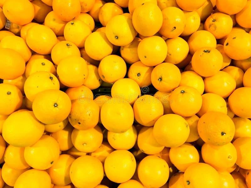 美好的黄色自然甜鲜美成熟软的回合明亮的明亮的蜜桔,果子,柑桔 纹理,背景 免版税库存图片