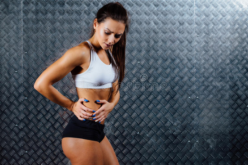 美好的年轻健身妇女感觉痛苦 免版税图库摄影