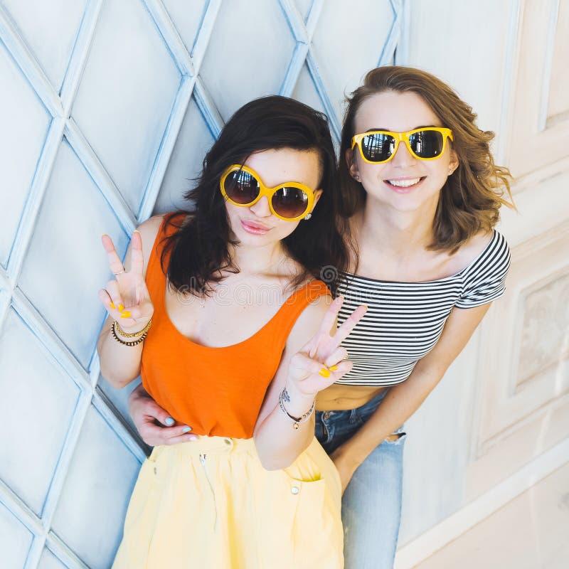 美好的年轻夫妇时兴的女孩白肤金发和深色在摆在和微笑为加州的一件明亮的黄色礼服和太阳镜 免版税库存照片