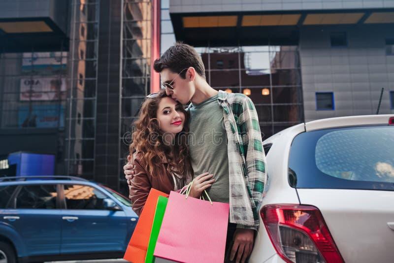 美好的年轻夫妇站立,并且在汽车附近的亲吻,做购物 免版税库存图片