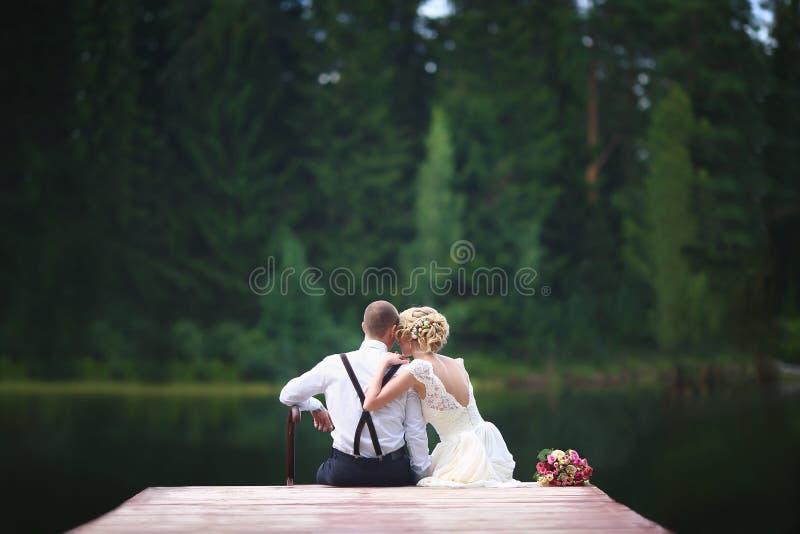 美好的年轻婚礼夫妇坐码头 免版税库存照片
