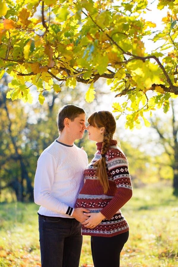 美好的年轻怀孕的夫妇有野餐在秋天公园 Ha 图库摄影