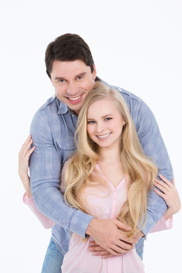 美好的年轻愉快的夫妇爱微笑的拥抱 免版税库存图片