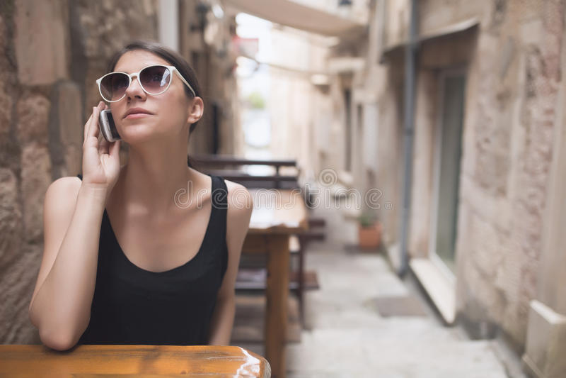 美好的黑暗棕褐色欧洲妇女谈话在有朋友闲话的电话 在咖啡馆的女商人谈的电话在老镇 免版税库存图片