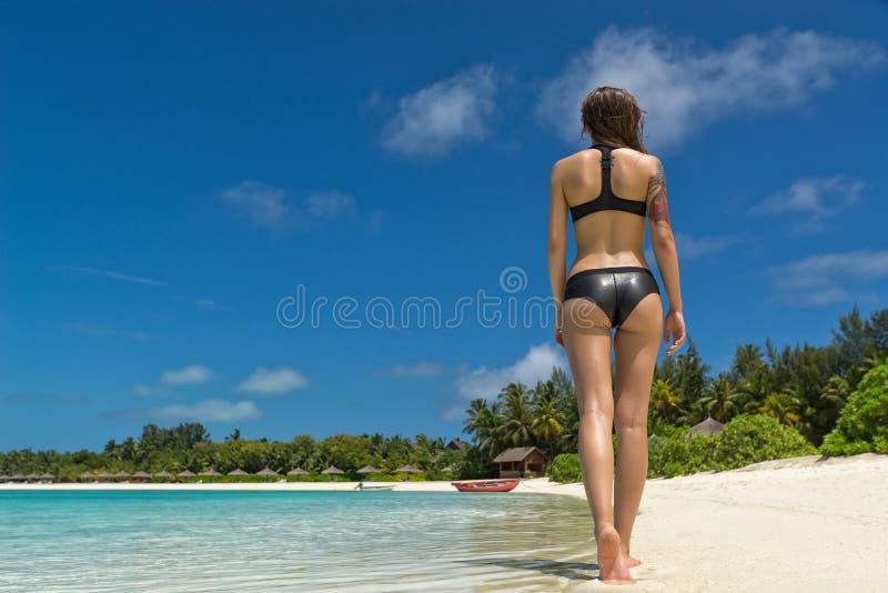 美好的woman& x27; 在性感的比基尼泳装的s身体在海滩背景 图库摄影