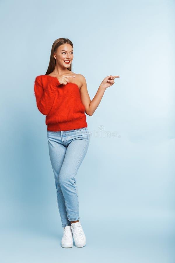 美好逗人喜爱惊人年轻女人摆在被隔绝在显示copyspace的蓝色墙壁背景 免版税库存照片