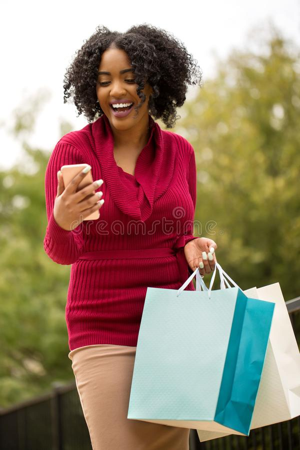 美好非裔美国人妇女购物和发短信 免版税图库摄影