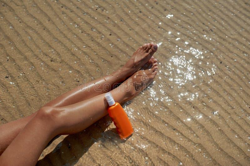 美好,修饰的妇女` s腿以保护晒斑的奶油免受太阳在背景海的夏天 关心 库存照片