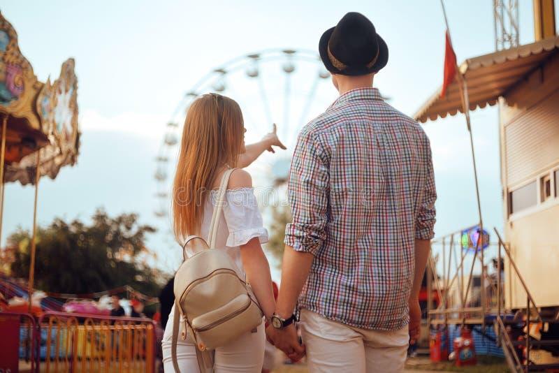美好,年轻夫妇获得乐趣在游乐园 夫妇约会放松爱主题乐园概念 一起摆在的夫妇 免版税图库摄影