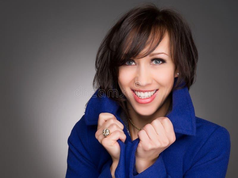 美好年轻和确信妇女微笑 佩带的深蓝冬天外套 免版税库存图片