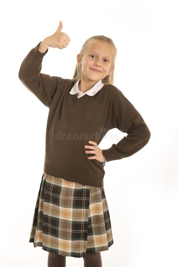 美好7或8的岁画象和愉快的在白色后面校服微笑的快乐的女小学生女孩隔绝的 免版税库存照片
