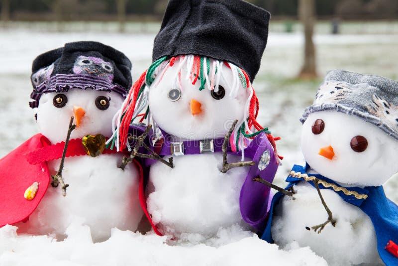 美妙地穿戴的三个时髦的雪人 库存图片