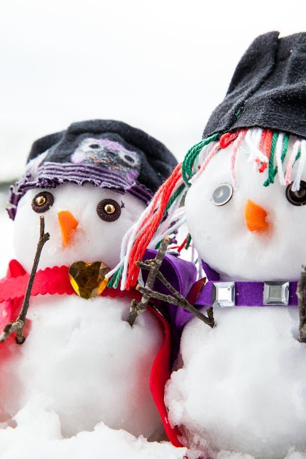 美妙地穿戴的两个时髦的雪人 库存图片