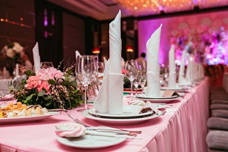 美妙地组织的活动,玻璃在准备好服务的欢乐白色的桌上 宴会,婚姻的装饰 利器和陶器 库存照片