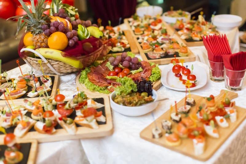 美妙地装饰的承办的宴会桌用另外食物 免版税图库摄影