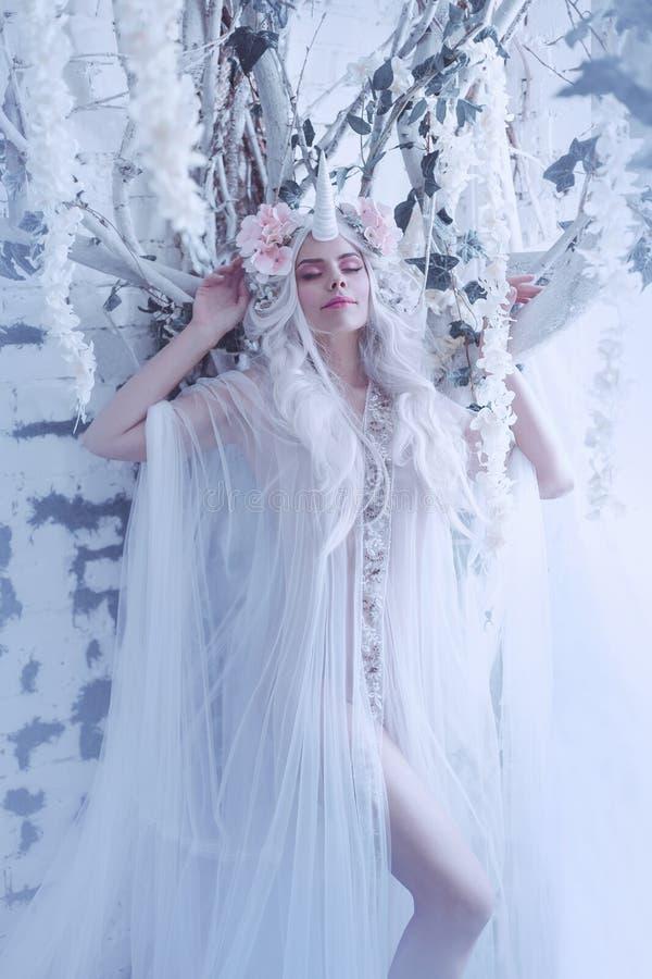 美妙的创作,女孩是在光,白色,有一点透明服装的一只独角兽 背景是一间明亮的屋子 免版税库存照片