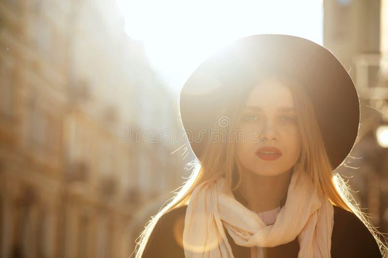 美妙的白肤金发的女孩佩带的帽子,围巾室外画象和 免版税库存图片