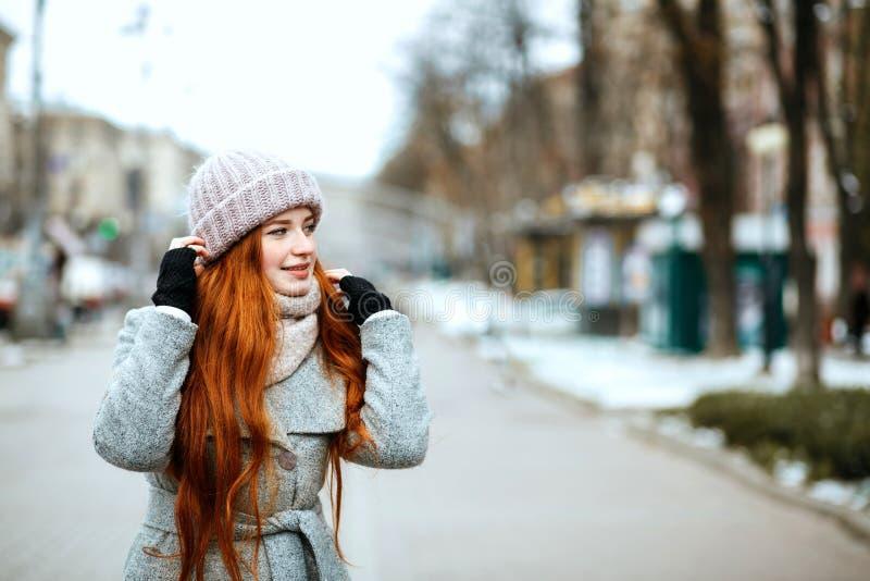 美妙的红头发人女孩都市画象有佩带w的长发的 库存图片
